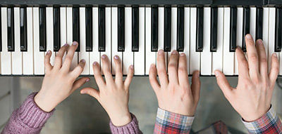 small and large hands playing piano